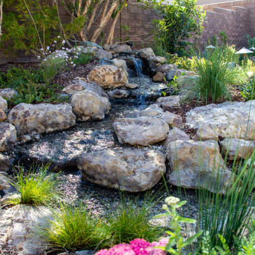 A custom water feature surrounded by pollinator friendly plants.